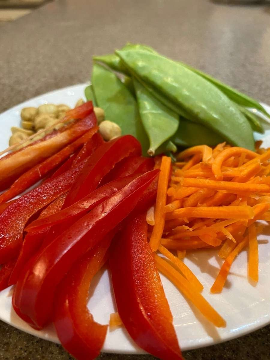 Bell peppers, carrots, snow peas, and roasted peanuts are excellent toppings.